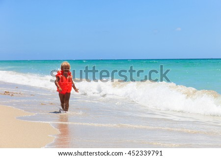 cute little girl in life jacket on summer beach, safety