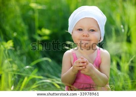 Cute little girl in meadow at sunny summer day - stock photo