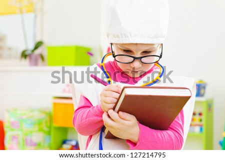 Cute little girl in medical uniform playing in doctor - stock photo