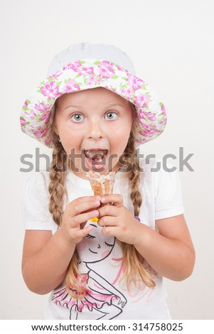 Cute little girl in panama eats an ice cream cone on a white background. Happy Caucasian child isolated on white background smiling. - stock photo