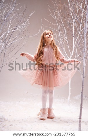 Cute little girl in pink dress walking in magic forest among bare trees - stock photo