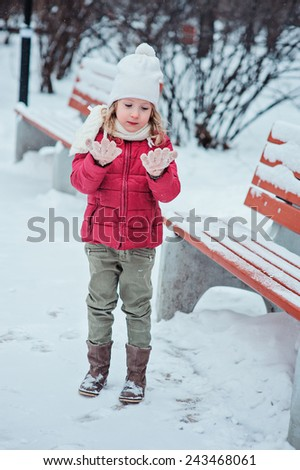 cute little girl in red coat and white hat on the walk in winter snowy park - stock photo