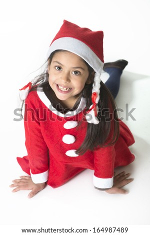Cute Little Girl in Santa Claus costume posing happy at Christmas