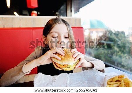 Cute little  girl in school uniform  eating a hamburger and potatoes in the restaurant - stock photo
