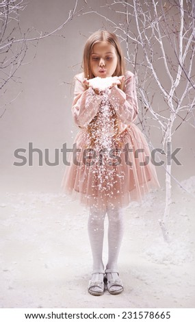 Cute little girl in smart dress blowing snowflakes from her palms in winter forest - stock photo