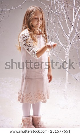 Cute little girl in smart dress looking at heap of snowflakes on her palm - stock photo