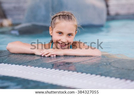 Cute little girl in swimming pool learning how to swim
