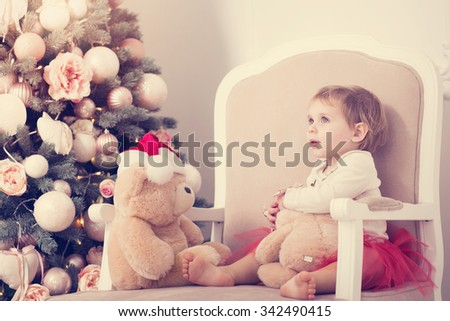 Cute little girl in the age of a little over a year old in a red skirt sitting in a chair with a teddybear on the background of a beautiful Christmas tree, New Year's Eve