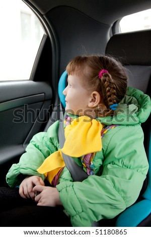 Cute little girl in the car. Traveling with safety. - stock photo