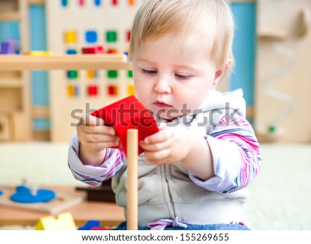 cute little girl in the classroom early development plays with bright toys - stock photo
