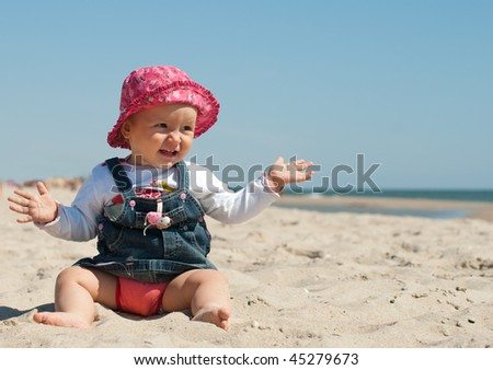 Cute little girl in the sun-hat sitting at the beach with her hands in the sand - stock photo