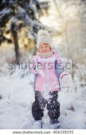 Cute little girl in the winter forest - stock photo