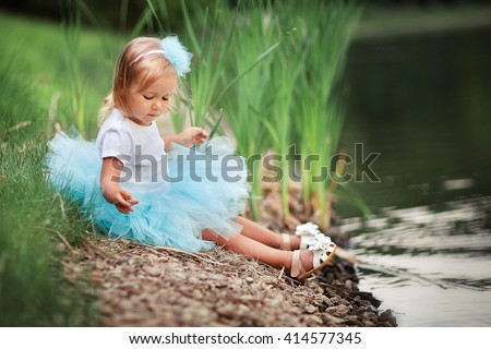 Cute little girl in turquoise tutu skirt sitting near the river and playing with pebbles. Adorable kid enjoying the nature. Fashion child joying in green summer park. - stock photo