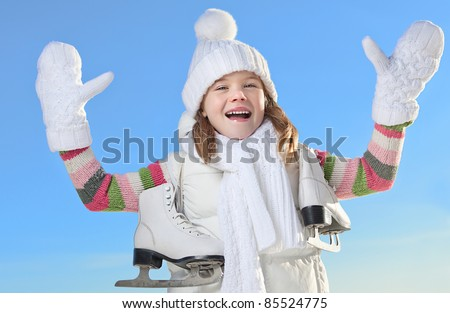 cute little girl in warm clothing outdoors with figure skates - stock photo