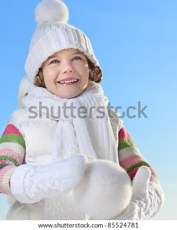 cute little girl in warm clothing outdoors with snowball - stock photo