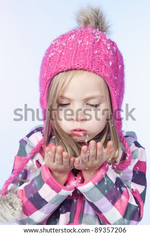Cute little girl in warm pink hat blowing snow on blue background - stock photo