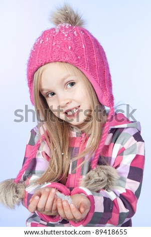 Cute little girl in warm pink hat holding snow on blue background - stock photo