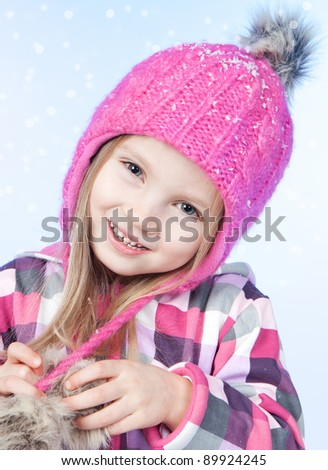 Cute little girl in warm pink hat on blue background - stock photo