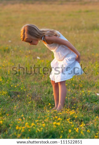 Cute little girl in white dress exploring the meadow on sunny spring day. - stock photo