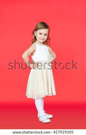 Cute little girl in white dress posing on red background. Full body portrait of cute kid in bright fashion outfit over vivid color wall. - stock photo