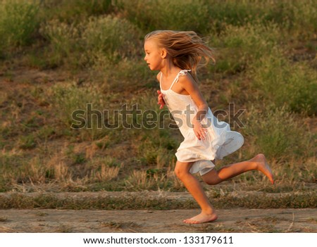 Cute little girl in white dress running on sunny spring day. - stock photo