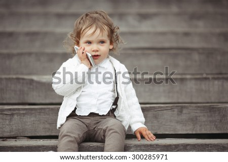 Cute little girl in white knitted sweater talking on mobile phone outdoors - stock photo