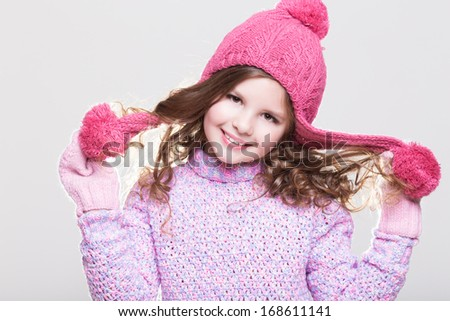 Cute little girl in winter woolen accessories. Adorable baby girl portrait in studio. Happy Little girl in winter hat and gloves. Space and white background.  - stock photo