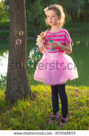 Cute little girl is blowing soap boubles