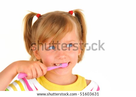 Cute little girl is brushing teeth with a smile - stock photo