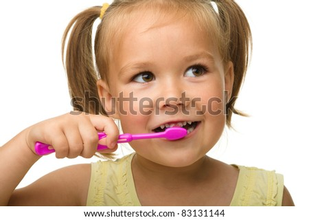 Cute little girl is cleaning teeth using toothbrush, isolated over white - stock photo