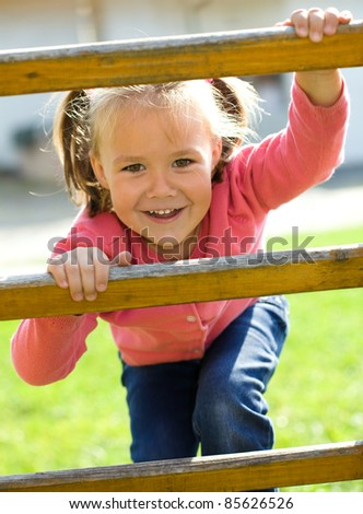 Cute little girl is climbing up on ladder in playground - stock photo