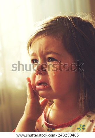 Cute little girl is crying. Toned - stock photo
