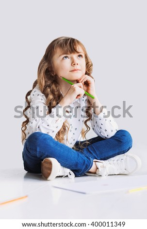 Cute little girl is drawing on a floor