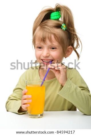 Cute little girl is drinking orange juice from one glass using straw, isolated over white - stock photo