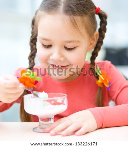 Cute little girl is eating ice-cream in parlor - stock photo