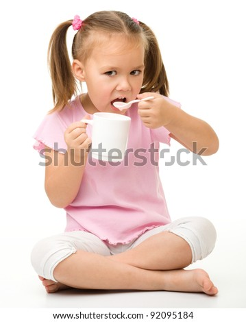 Cute little girl is eating yogurt from cup using spoon while sitting on floor, isolated over white - stock photo