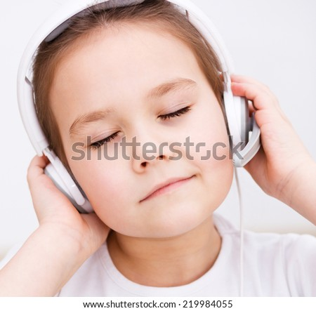 Cute little girl is enjoying music using headphones and closed her eyes - stock photo