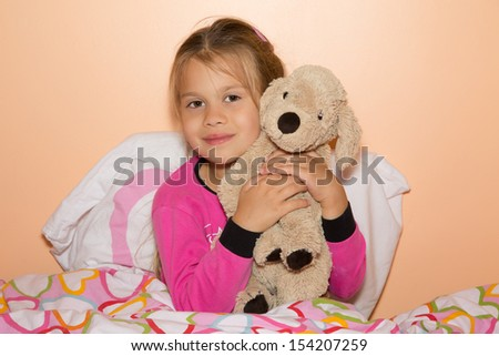 Cute little girl is getting ready to get to bed and hugging a plush dog - stock photo