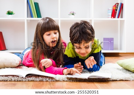 Cute little girl is helping to a little boy with their homework.Teamwork - stock photo
