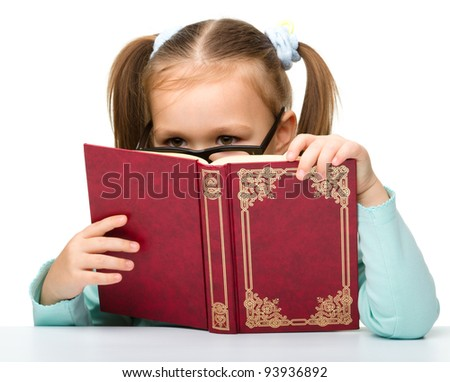 Cute little girl is hiding behind a book while sitting at table, isolated over white - stock photo
