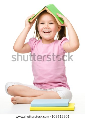 Cute little girl is hiding under a book, isolated over white - stock photo