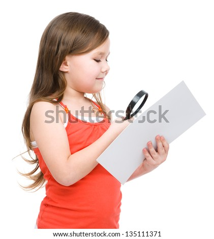 Cute little girl is looking at big paper sheet through magnifier, isolated over white - stock photo
