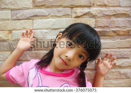 Cute little girl is looking at camera - stock photo