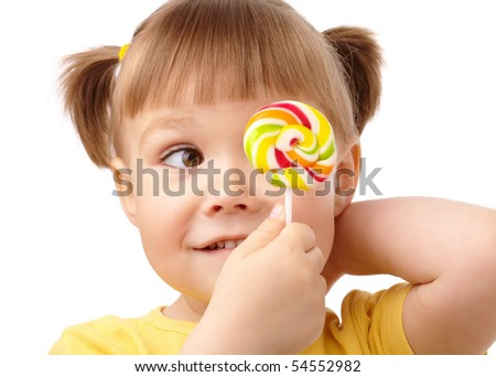 Cute little girl is looking at her colorful lollipop, isolated over white - stock photo