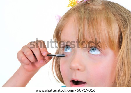 Cute little girl is painting eyelashes - stock photo