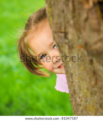 Cute little girl is playing hide and seek outdoors - stock photo