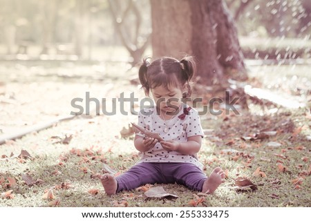 Cute little girl is playing in the park in vintage style - stock photo