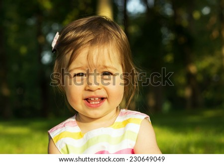 cute little girl is playing on send in sunny day  - stock photo