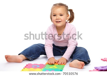 Cute little girl is playing with alphabet, putting hands up while sitting on floor, isolated over white