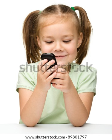 Cute little girl is playing with cell phone while sitting at table, isolated over white - stock photo